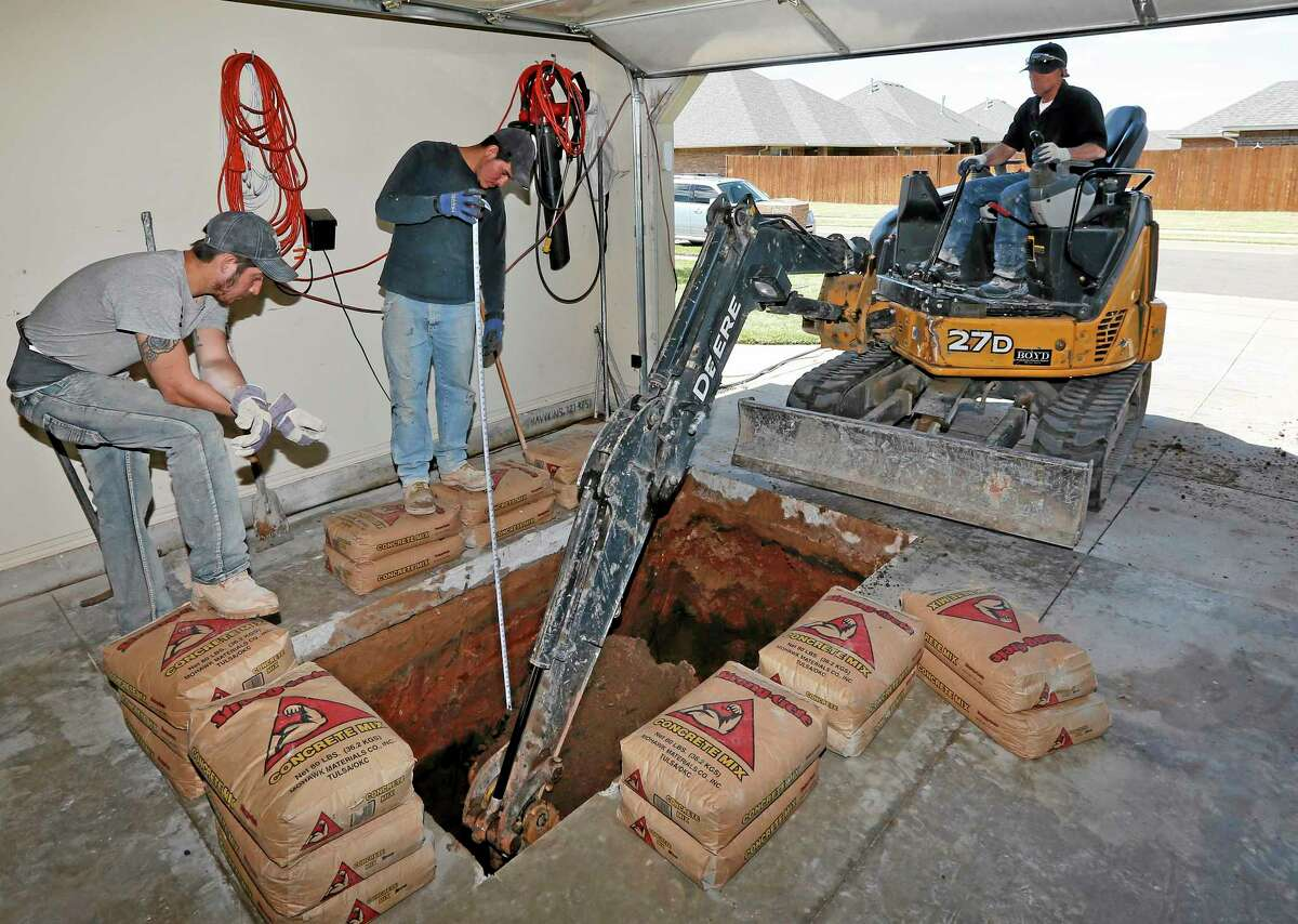 Thunderground Storm Shelters' Dustin Wagner, left, and Jacob Ortiz, center, assist as Jim Hohnsbehn digs a hole for a storm shelter in the garage at a residence in Oklahoma City earlier this month.