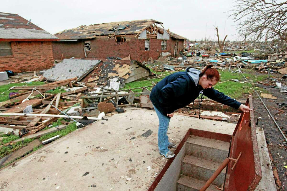 In this May 24, 2013, photo, Sabrina Mitchell takes a peek inside a neighbor's storm shelter in Moore, Oklahmoa.
