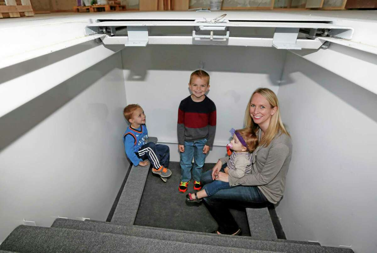 Tessa Beaulieu poses for a photo in the storm shelter of her new construction home with her children, from left, Hudson, Dawson and Sloane, in Edmond, Oklahoma, earlier this month.