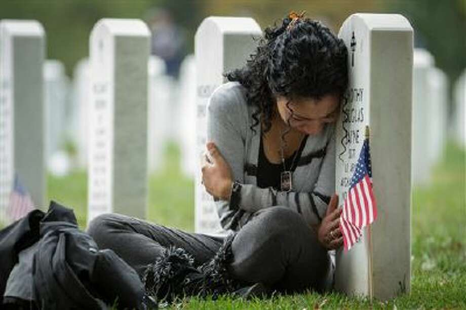 Thania Sayne of Effingham, Ill., leans on the headstone at the grave of her husband, Army Sgt. Timothy D. Sayne, during the playing of taps at a nearby burial service at Arlington National Cemetery, in Arlington, Va., on Oct. 16, a day before what would have been their third wedding anniversary. Sayne was 4 months pregnant with their second son, Douglas, when her husband was killed on Sept. 18, 2011, in the Kandahar province of Afghanistan. Photo: AP / AP