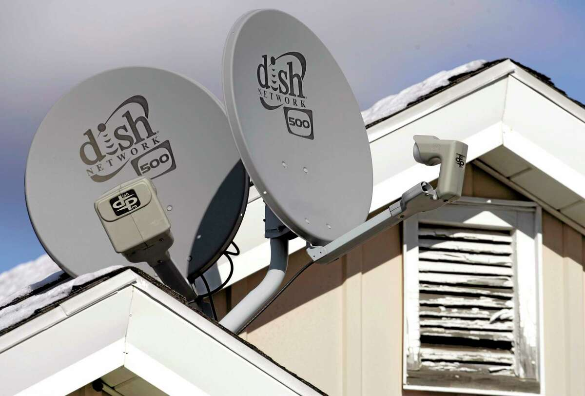 In this 2008 photo, Dish Network Corp. satellite dishes are attached to a home in Buffalo, New York.