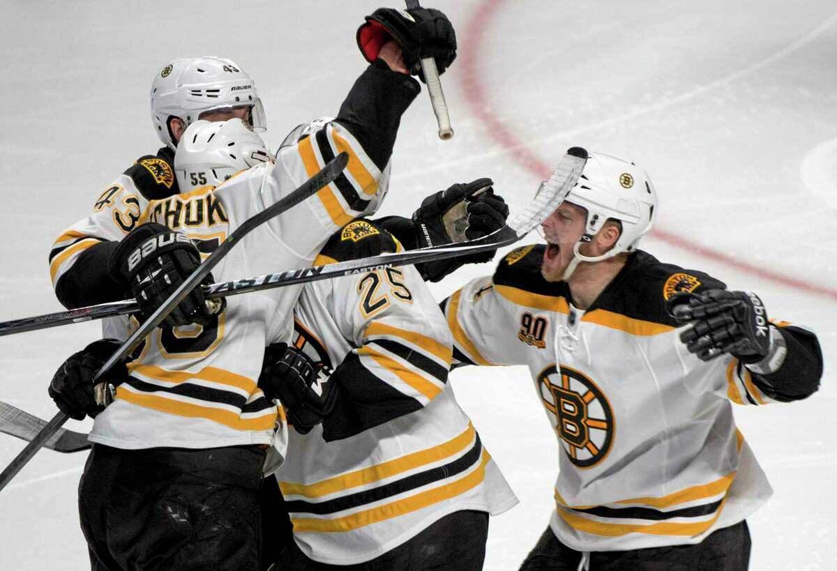 Members of the Boston Bruins crowd around Matt Fraser (25) following his game-winning goal against the Canadiens during overtime in Game 4 in the second round of the Stanley Cup playoffs on Thursday in Montreal.