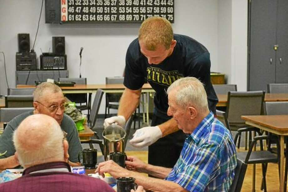 Titans right fielder and Goshen native, Michael Odenwaelder pours tea for members of the Sullivan Senior Center. Pete Paguaga-Register Citizen