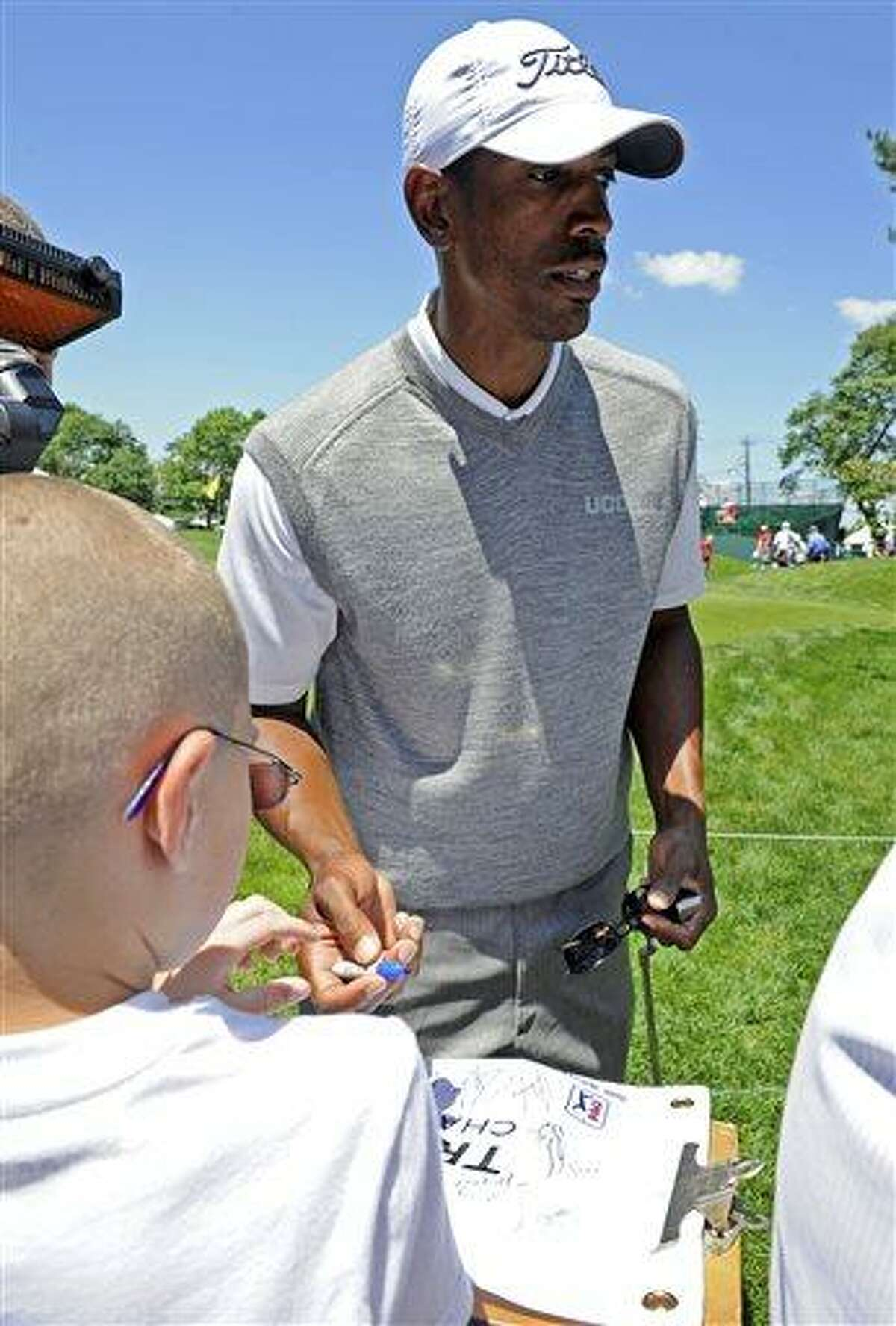 Kevin Ollie, Connecticut men's basketball coach, signs autographs after completing his round in the pro-am at the Travelers Championship golf tournament in Cromwell, Conn., Wednesday, June 19, 2013. (AP Photo/Fred Beckham)