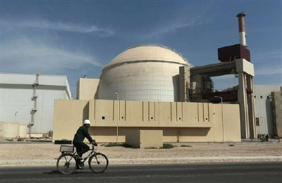 A worker rides a bicycle in front of the reactor building of the Bushehr nuclear power plant, just outside the southern city of Bushehr. Iran. Photo: ASSOCIATED PRESS / AP2014