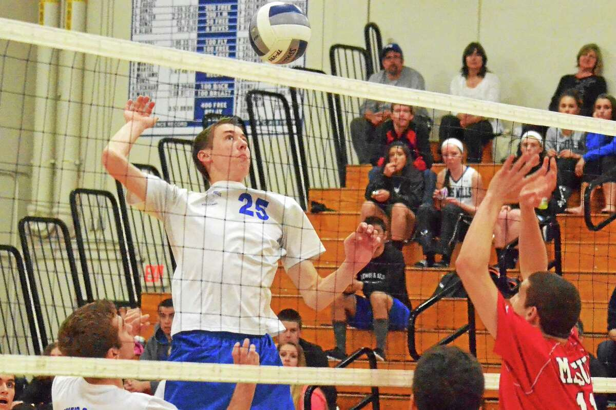 Pete Paguaga - Register Citizen Lewis Mills' Tim Forella spikes the ball in the Spartans' 3-1 loss to Masuk.