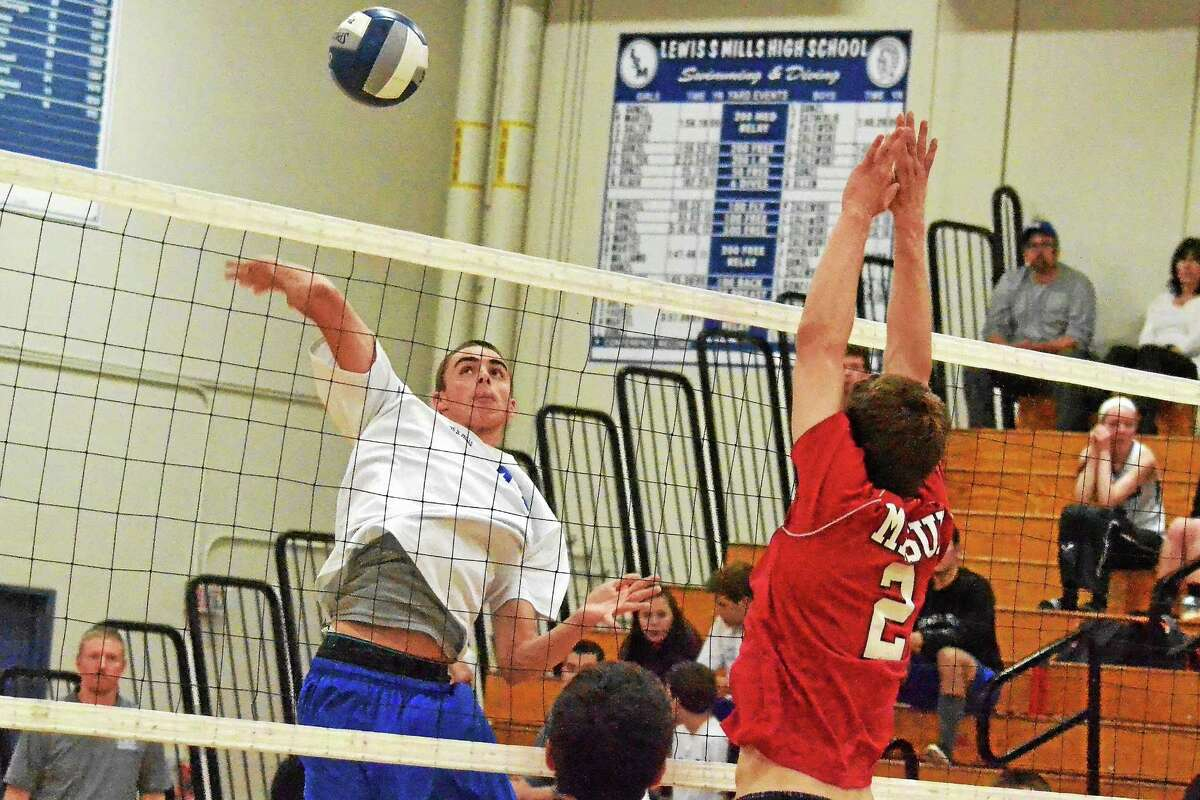 Pete Paguaga - Register Citizen Lewis Mills' Alexander Daigle spikes the ball as Masuk's John O'Shaughnessy goes up for the block.