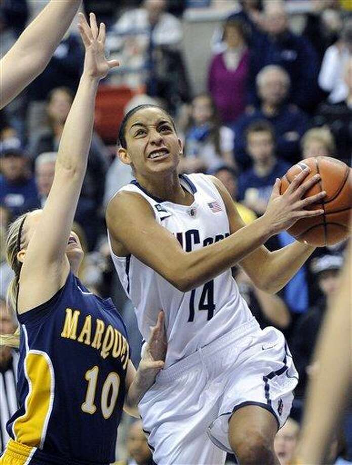 Connecticut's Bria Hartley, right, drives past Marquette's Brooklyn Pumroy during the first half of an NCAA college basketball game in Storrs, Conn., Tuesday, Feb. 5, 2013. (AP Photo/Fred Beckham) Photo: ASSOCIATED PRESS / AP2013