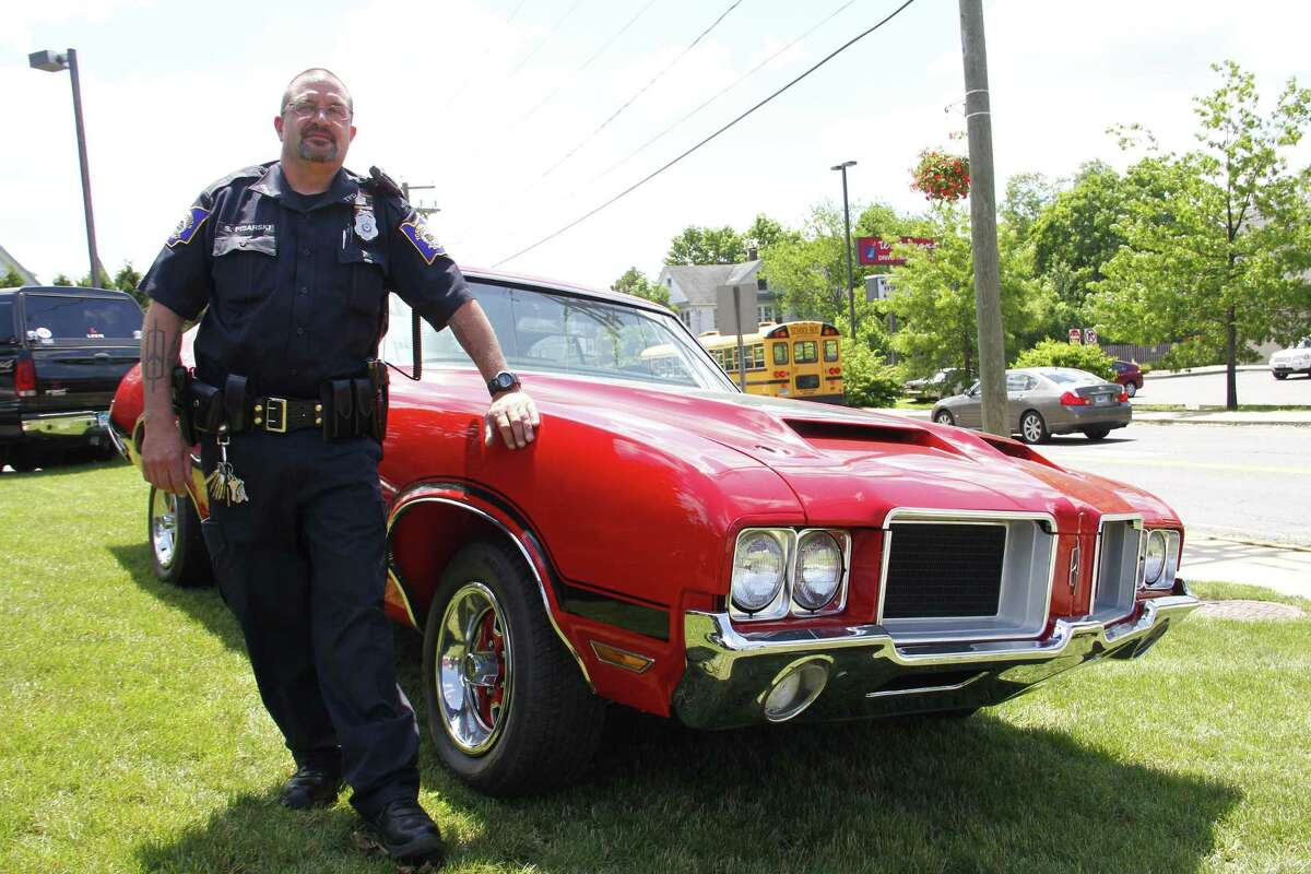 Officer Steve Pisarski stands next to his 1971 Oldsmobile 442 outside the Torrington Police Department on Wednesday, June 19, 2013. Pisarski is helping organize the Torrington Police Department Auto Show, which will take place on Friday starting at 5:30 p.m. on Main Street in Downtown. His car will be in the show, and more than 300 cars are expected. Esteban L. Hernandez Register Citizen