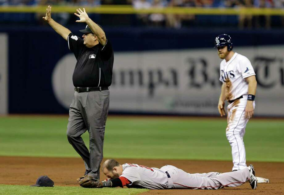 Boston Red Sox second baseman Dustin Pedroia lies injured after colliding with the Tampa Bay Rays' Logan Forsythe on Saturday in St. Petersburg, Fla. Photo: Chris O'Meara — The Associated Press  / AP