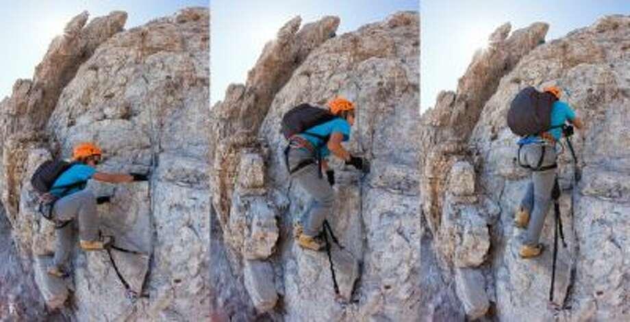 Ayoung boy climbs a via ferrata in the italian dolomites.