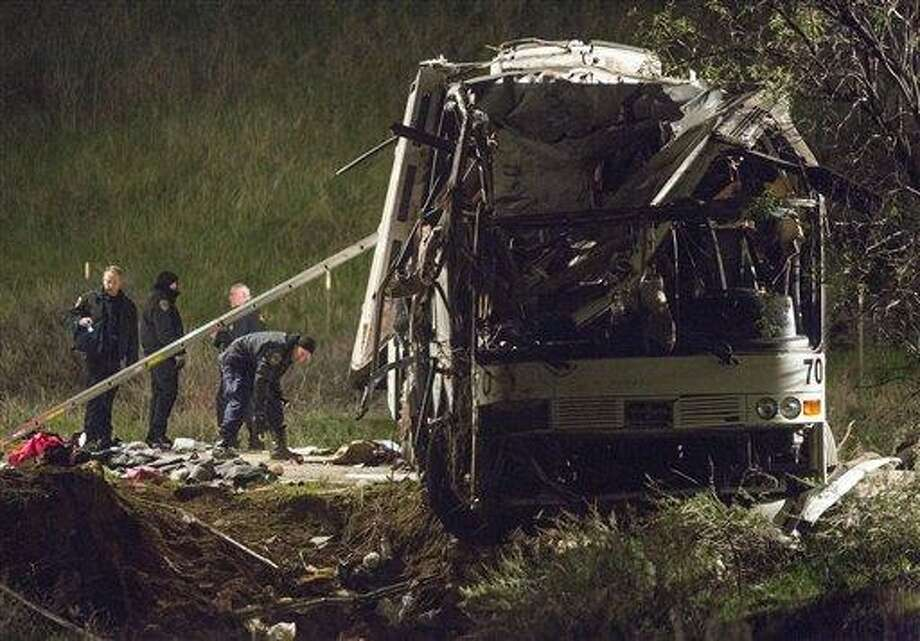 Investigators work at the scene, early Monday of the accident where at least eight people were killed and 38 people were injured Sunday after a tour bus carrying Mexican tourists careened out of control while traveling down a mountain road, striking a car, flipping and plowing into a pickup truck, near Yucaipa, Calif. AP Photo/Ringo H.W. Chiu Photo: AP / FR170512 AP