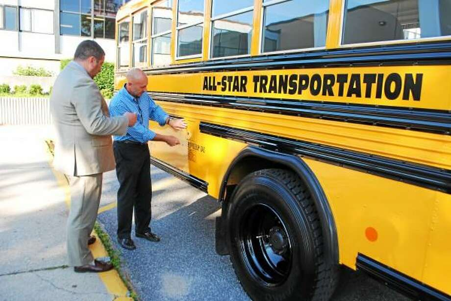 State Rep. Jay Case (R-Winchester) stands with a co-owner of All Star Transportation, John Dufour, looking at the new propane buses. (Jessica Glenza-Register Citizen)