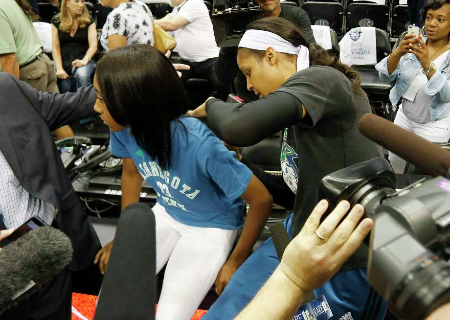 Minnesota Lynx forward Maya Moore signs Little League World Series pitcher Mo'ne Davis' shirt prior to Game 2 of the WNBA Western Conference finals on Sunday in Minneapolis. Photo: Stacy Bengs — The Associated Press  / FR170489 AP