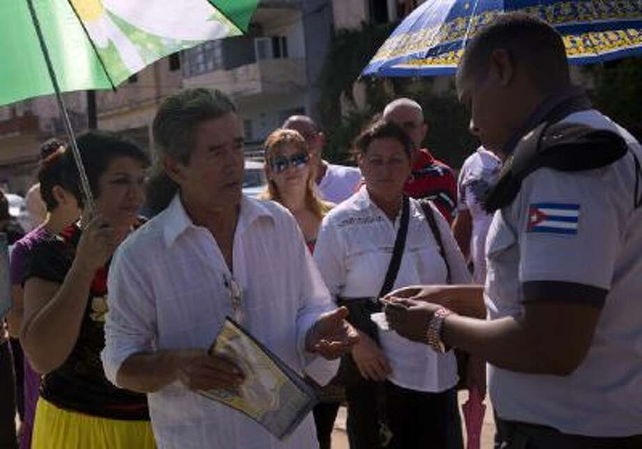 In this photo taken Jan. 13, 2014, Cuban police check identity cards of people waiting their turn to enter the U.S. Interests Section in Havana to apply for U.S. travel visas. Cubans are taking advantage of a travel reform that went into effect a year ago, when the government scrapped an exit visa requirement that for five decades had made it difficult for most islanders to go abroad.
