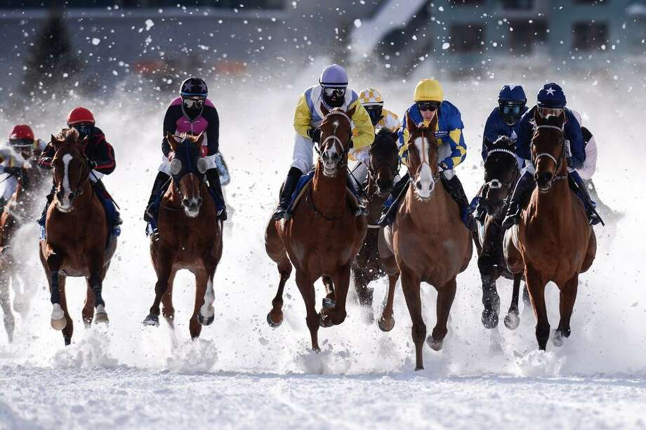 """Riders and horses compete during the Grand Prix """"Guardaval Immobilien"""" on the first weekend of the White Turf races in St. Moritz, Switzerland, Sunday, Feb., 3, 2013. (AP Photo/Keystone,Samuel Truempy) Photo: AP / KEYSTONE"""