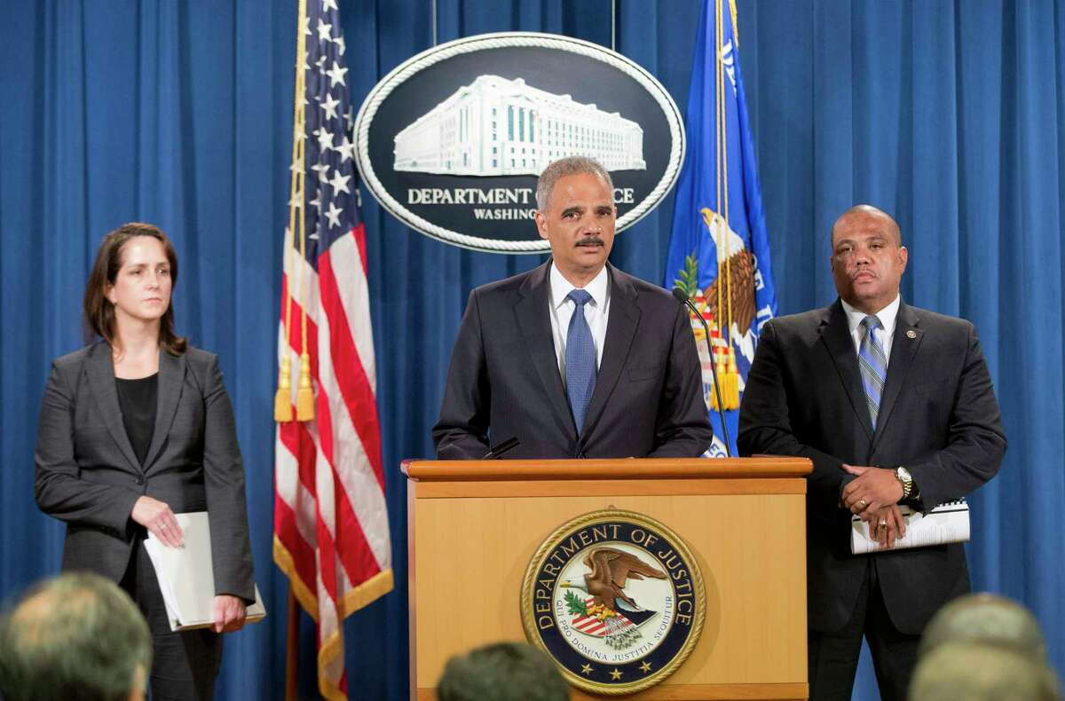 Attorney General Eric Holder, center, accompanied by Acting Assistant Attorney General for Civil Rights Division Molly Moran, left, and Ronald Davis, director of the Office of Community Oriented Policing Services (COPS), speaks during a news conference at the Justice Department in Washington, Thursday, Sept. 4, 2014, to announce the Justice Department's civil rights division will launch a broad civil rights investigation in the Ferguson, Mo.