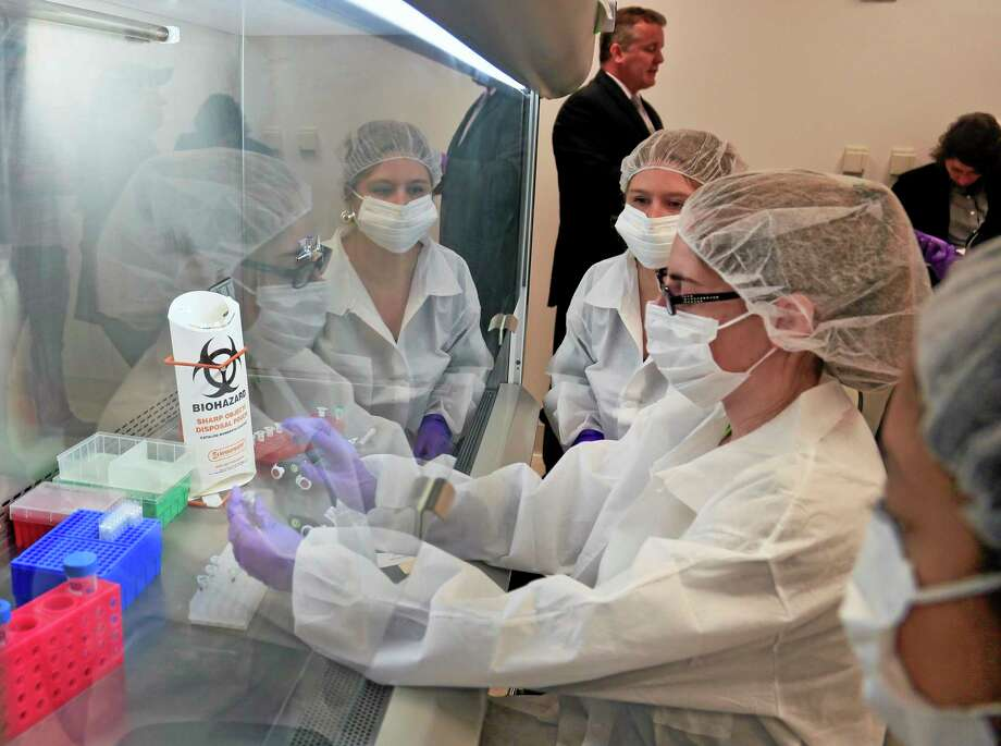 In this April 15, 2014 photo, Mark Desire, left, assistant director for forensic biology at the Office of Chief Medical Examiner, visits as criminalist trainees as they prepare sample bone fragments for DNA testing at the training lab in New York. With new technology yielding results impossible a dozen years ago, forensic scientists are still trying to match the bone with DNA from those who died on Sept. 11, 2001, and have never been identified. (AP Photo/Bebeto Matthews) Photo: AP / AP