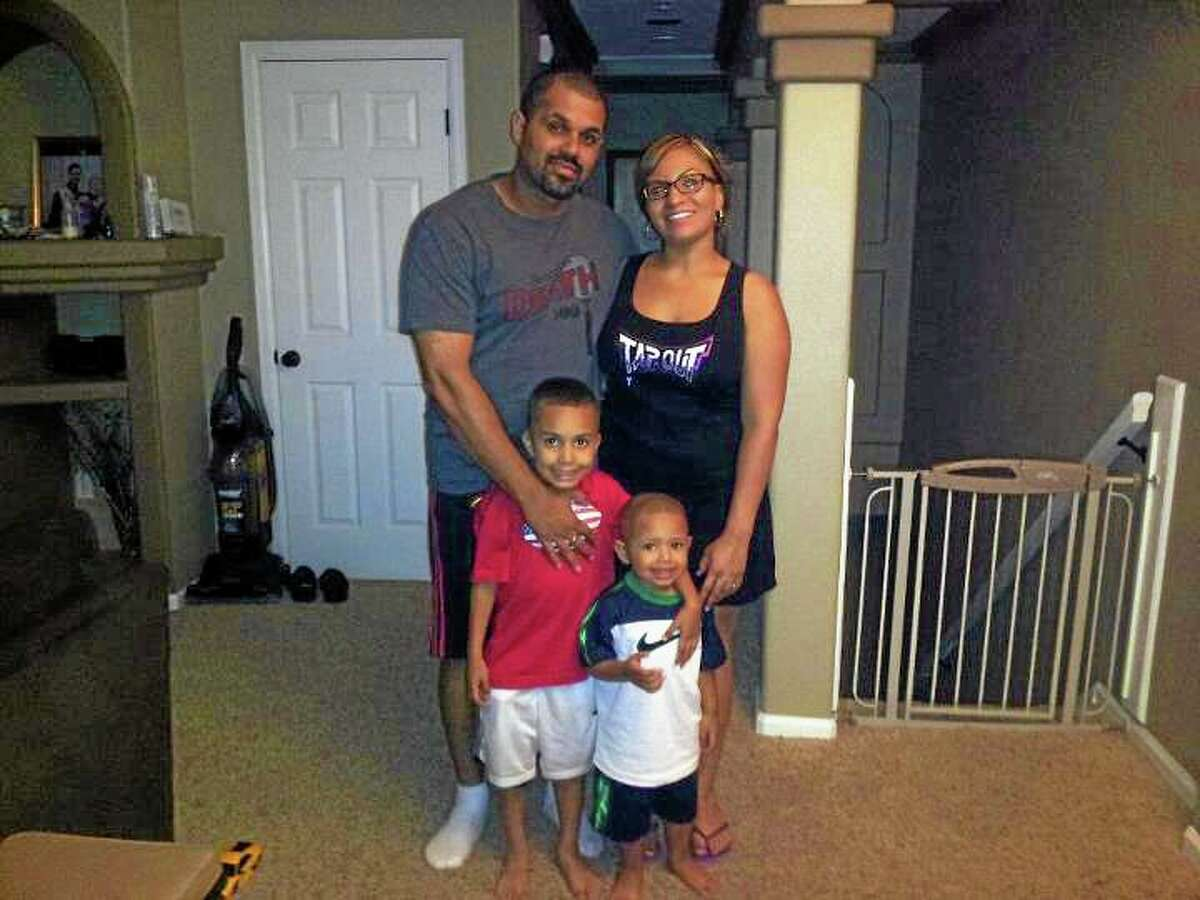 In this undated family photo provided by the Lima-Marin Family, Rene Lima Marin stands with his wife Jasmine and children Justus, 7, and Josiah, 4, at their home in Aurora, Colo. Rene Lima-Marin was sentenced in 2000 for a conviction in a robbery, kidnapping and burglary after robbing two Aurora video stores when Marin was 18. Marin was to stay in prison the rest of his life and serve 98 years. He was released after just 8 years due to a clerical error, living a crime-free life for six years before being sent back after authorities discovered their mistake. (AP Photo/Lima-Marin Family)