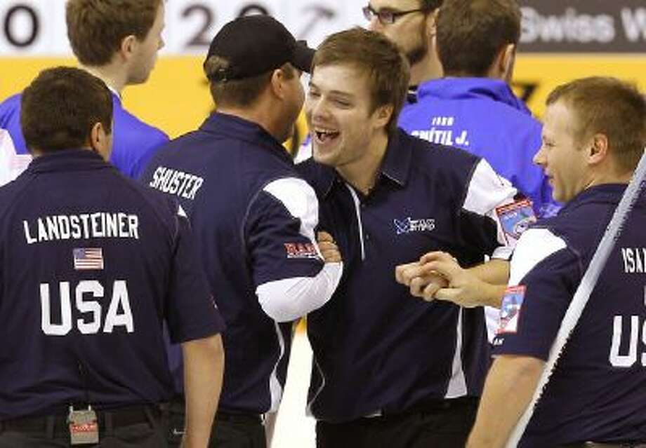 U.S. curling team members from left: John Landsteiner, John Shuster, Jared Zezel and Jeff Isaacson celebrate after qualifying for the 2014 Olympics during an Olympic qualification tournament in Fuessen, Germany, Dec. 15, 2013.