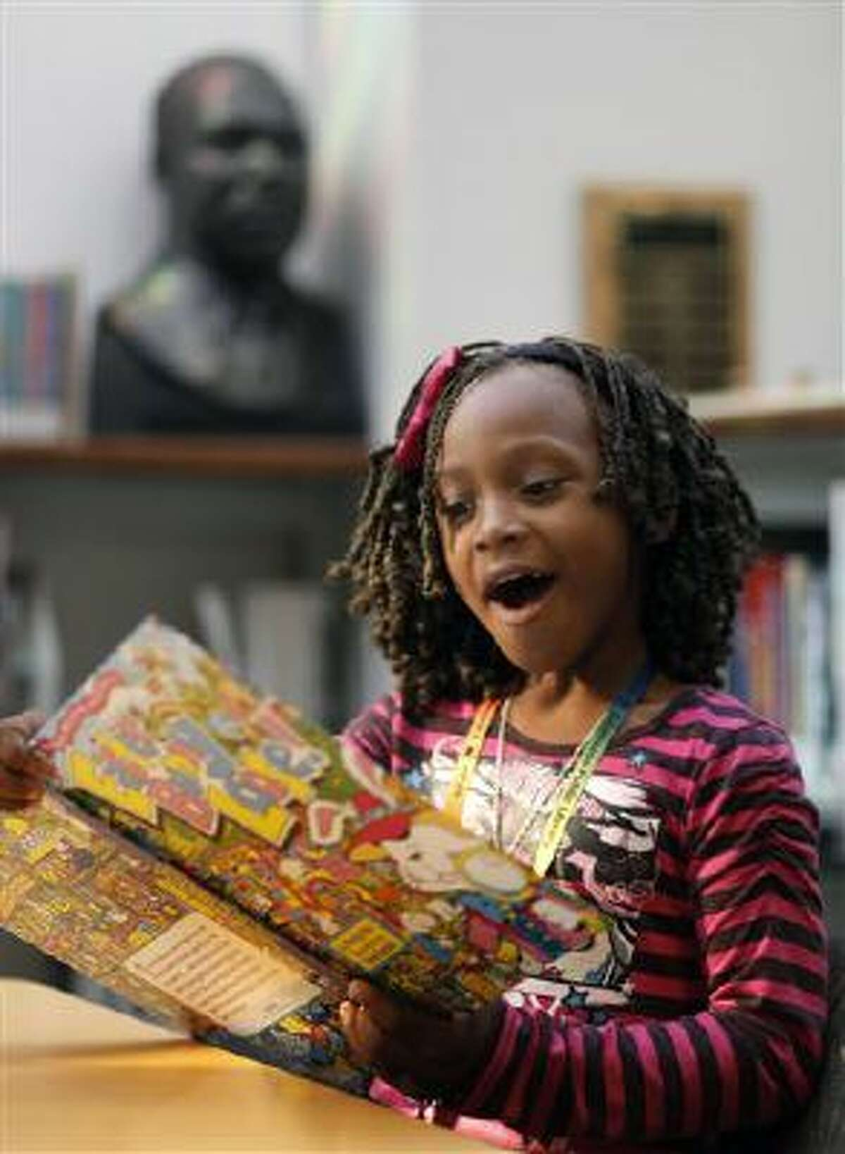 First-grade student Trevahya Whitfield looks at a book during a visit to the library in Kalamazoo, Mich. It is the third year of an ambitious partnership between Kalamazoo Public Schools and the Kalamazoo Public Library that aims to promote books and literacy. (AP Photo/Kalamazoo Gazette-MLive Media Group, Mark Bugnaski)