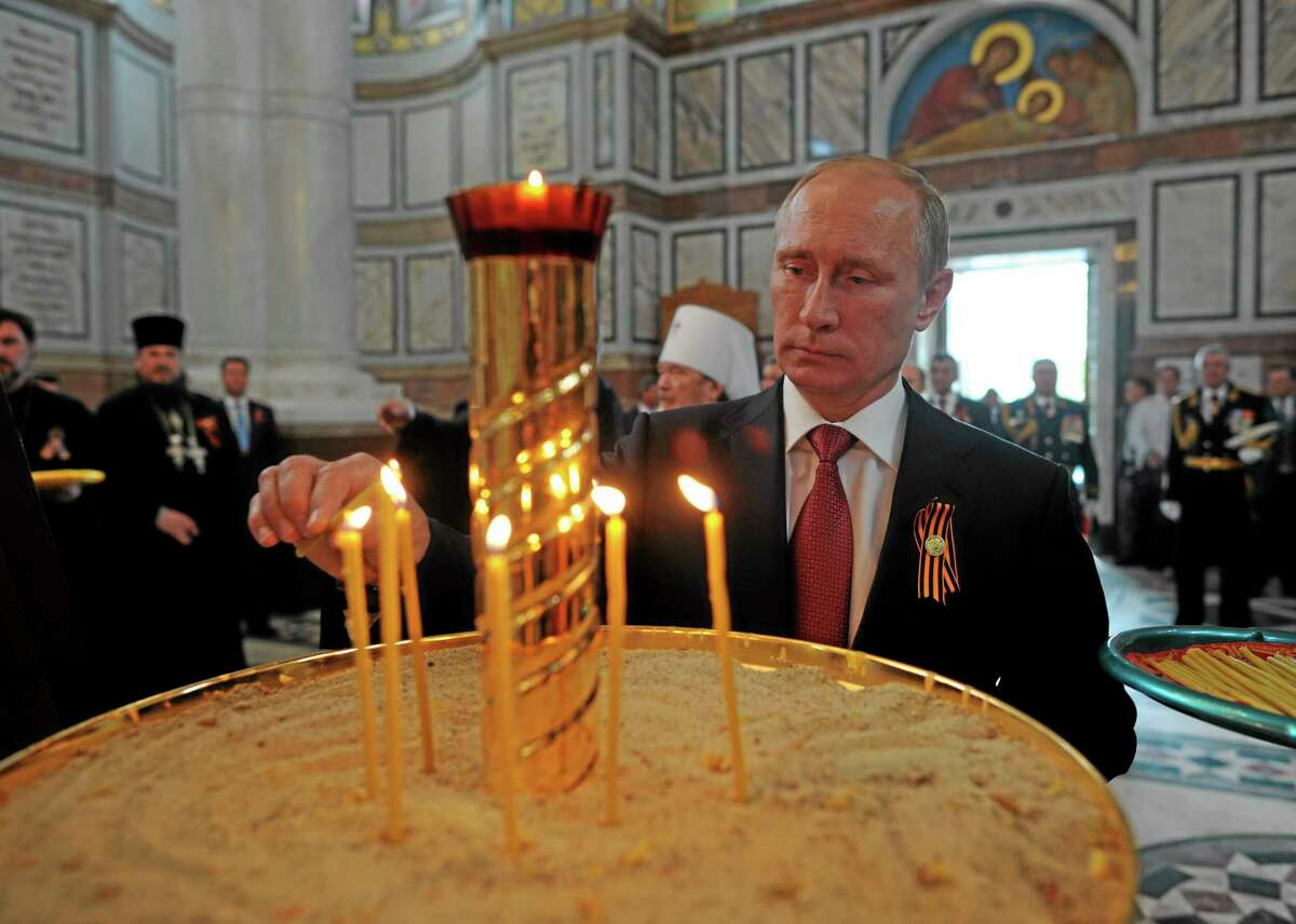 Russian President Vladimir Putin lights a candle in Sevastopol where he attends celebrations marking the Victory Day, in Crimea, Friday, May 9, 2014. President Vladimir Putin hailed the return of Crimea to Russia as the restoration of
