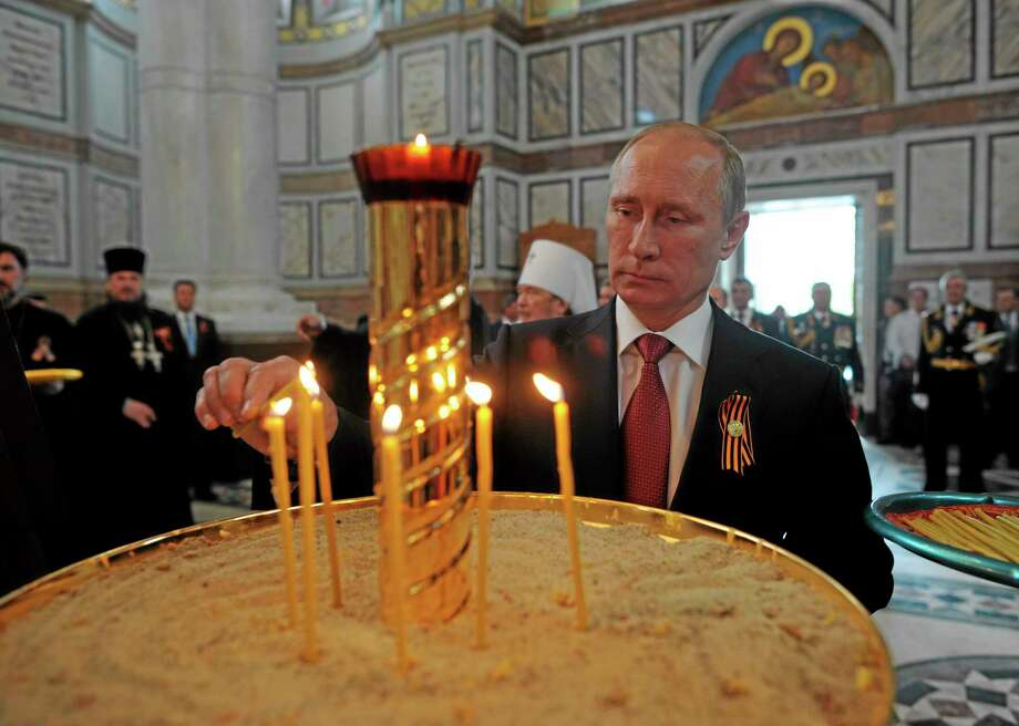 "Russian President Vladimir Putin lights a candle in Sevastopol where he attends celebrations marking  the Victory Day, in Crimea, Friday, May 9, 2014. President Vladimir Putin hailed the return of Crimea to Russia as the restoration of ""historic justice"" before a jubilant, welcoming crowd Friday on the holiday that Russians hold dearest. Putin's visit to the Crimean port of Sevastopol, was strongly criticized by both NATO and Ukraine's Foreign Ministry. (AP Photo/RIA-Novosti, Alexei Druzhinin, Presidential Press Service) Photo: AP / RIA Novosti Kremlin"