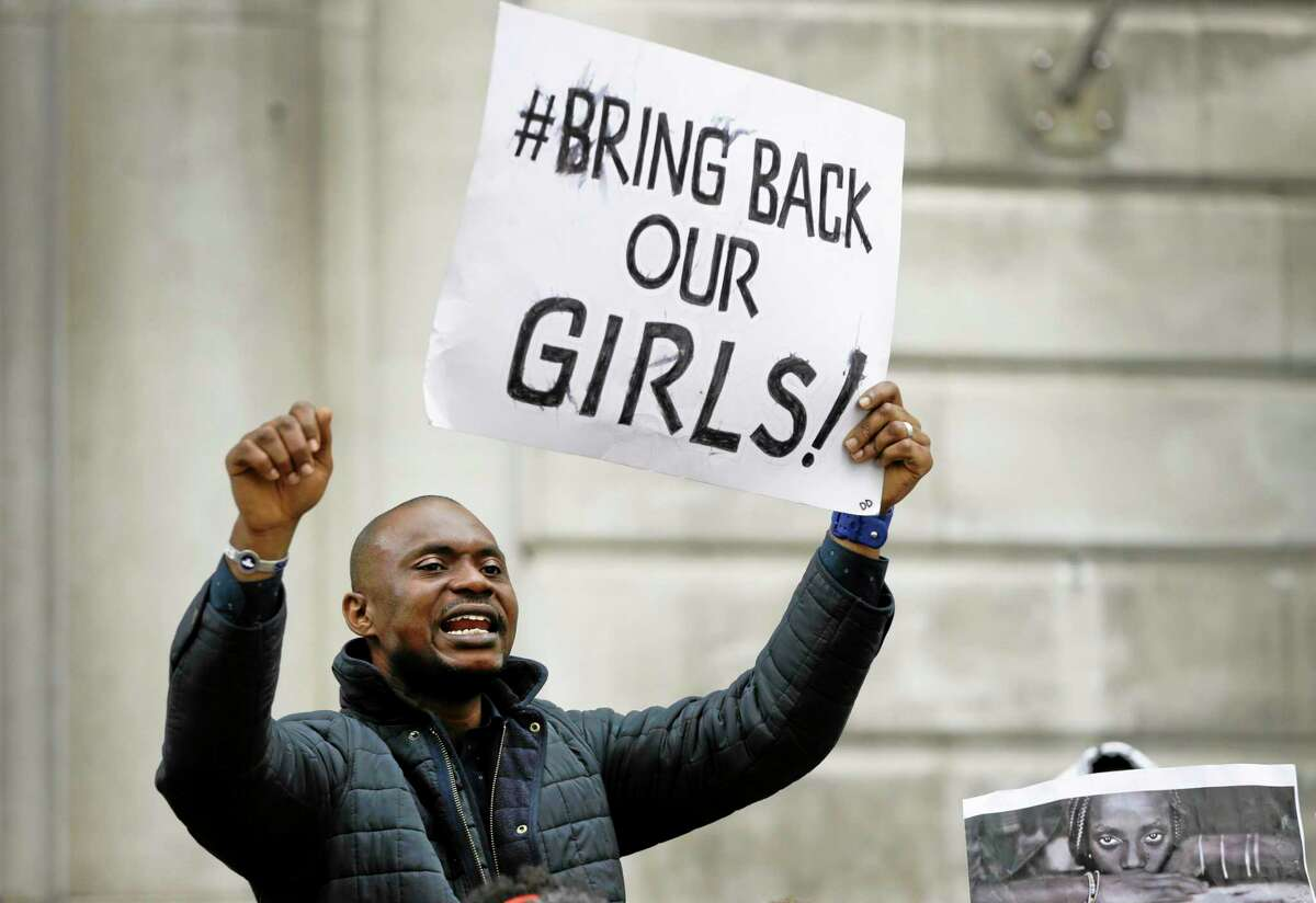 A demonstrator holds a banner, during a protest about the kidnapping of girls in Nigeria, near the Nigerian High Commission in London, Friday, May 9, 2014. Global outrage against the abduction of more than 200 Nigerian girls by Islamist militant sect Boko Haram heated up Thursday, as a social media campaign drew worldwide support. (AP Photo/Kirsty Wigglesworth)