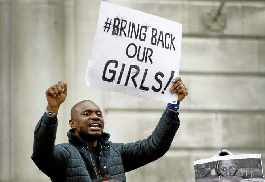 A demonstrator holds a banner, during a protest about the kidnapping of girls in Nigeria, near the Nigerian High Commission in London, Friday, May 9, 2014. Global outrage against the abduction of more than 200 Nigerian girls by Islamist militant sect Boko Haram heated up Thursday, as a social media campaign drew worldwide support. (AP Photo/Kirsty Wigglesworth) Photo: AP / AP
