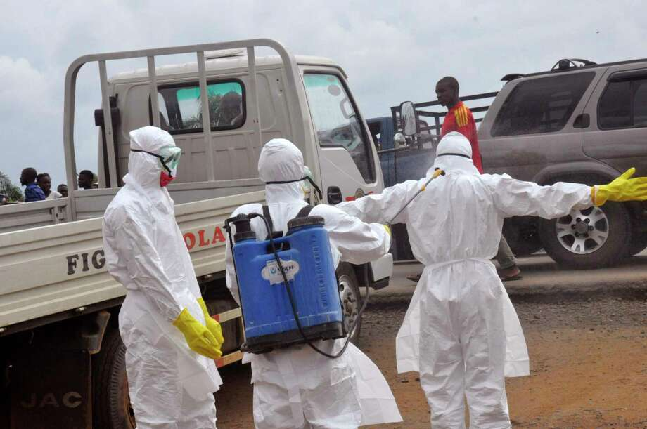 Health worker's spray each other with disinfectant chemicals as they worked with a suspected  Ebola virus death in Monrovia, Liberia, Thursday, Sept. 4, 2014. As West Africa struggles to contain the biggest ever outbreak of Ebola, some experts say an unusual but simple treatment might help: the blood of survivors. The evidence is mixed for using infection-fighting antibodies from survivors' blood for Ebola, but without any licensed drugs or vaccines for the deadly disease, some say it's worth a shot. Photo: (AP Photo/Abbas Dulleh) / AP