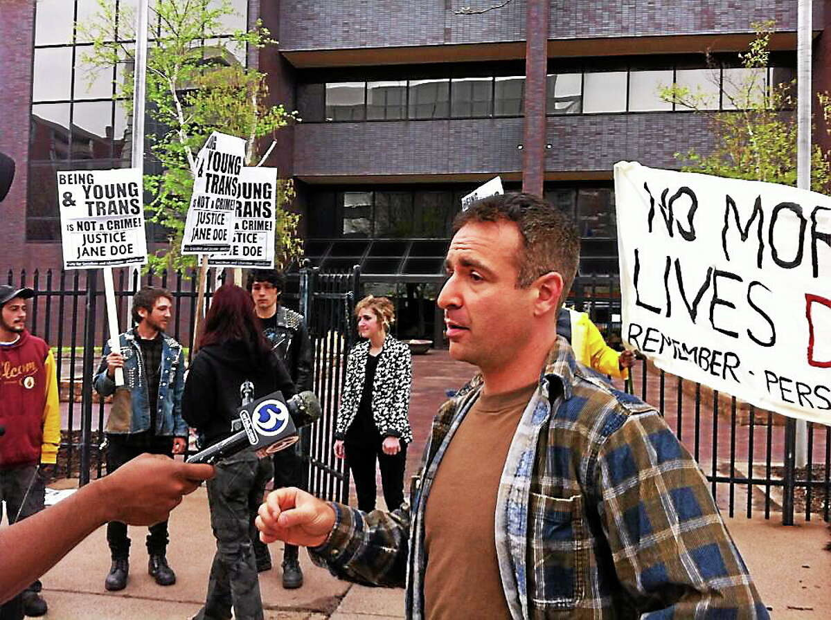 Jane Doe's attorney, Aaron Romano, speaks to a reporter at a protest against his teen client's incarceration in an adult prison in Connecticut.
