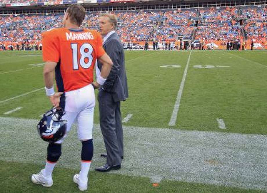 Denver Broncos quarterback Peyton Manning stands on the sidelines next to John Elway.