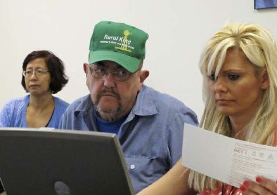 In this Oct. 1, 2013 photo, Patrick Lamanske of Champaign, Ill., works with Amanda Ziemnisky, right, of the Champaign Urbana Public Health District office in Champaign to try to sign his wife, Ping Lamanske, left, up for health care coverage through the Affordable Care Act.