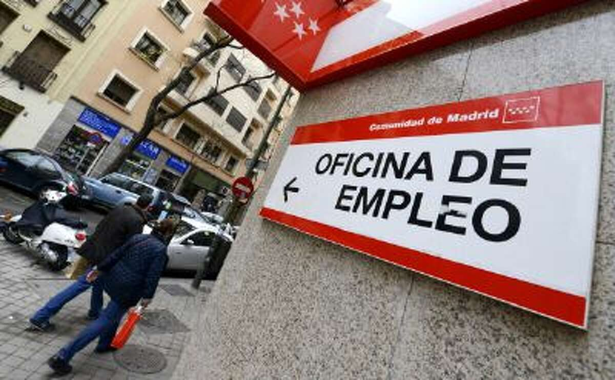 People walk outside a government employment office in the center of Madrid on Jan. 3. Spain announced today a sharp contraction in jobless queues in December, offering a glimmer of New Year hope for the 4.7 million people still registered as unemployed in the eurozone's fourth-largest economy.