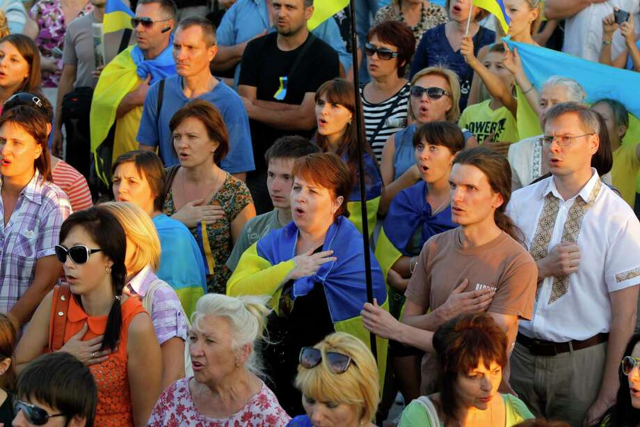 People sing the national anthem during an anti-war meeting in the town of Mariupol, eastern Ukraine, Thursday, Sept. 4, 2014. Separatist rebels have made major strides in their offensive against Ukrainian government forces in recent days, drawing on what Ukraine and NATO says is ample support from the Russian military. (AP Photo/Sergei Grits) Photo: AP / AP