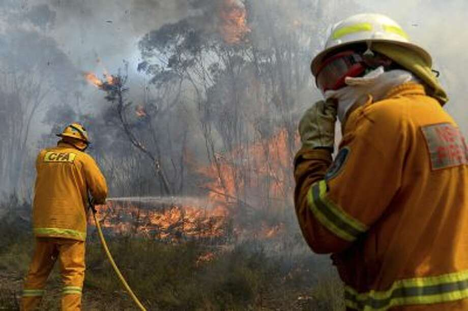 Firefighters work on putting in containment lines to help control a wildfire near the township of Bell, Australia. Photo: AP / AAP