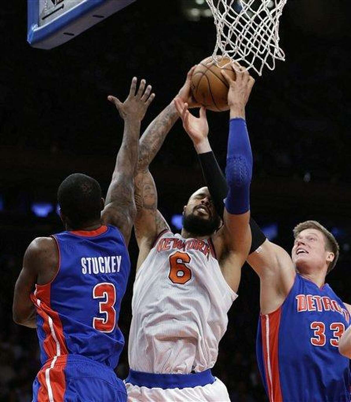 New York Knicks center Tyson Chandler (6) grabs a rebound as Detroit Pistons guard Rodney Stuckey (3) and forward Jonas Jerebko (33) of Sweden try to get the ball back beneath the Pistons' basket in the second half of an NBA basketball game at Madison Square Garden in New York, Monday, Feb. 4, 2013. The Knicks won 99-85. (AP Photo/Kathy Willens)