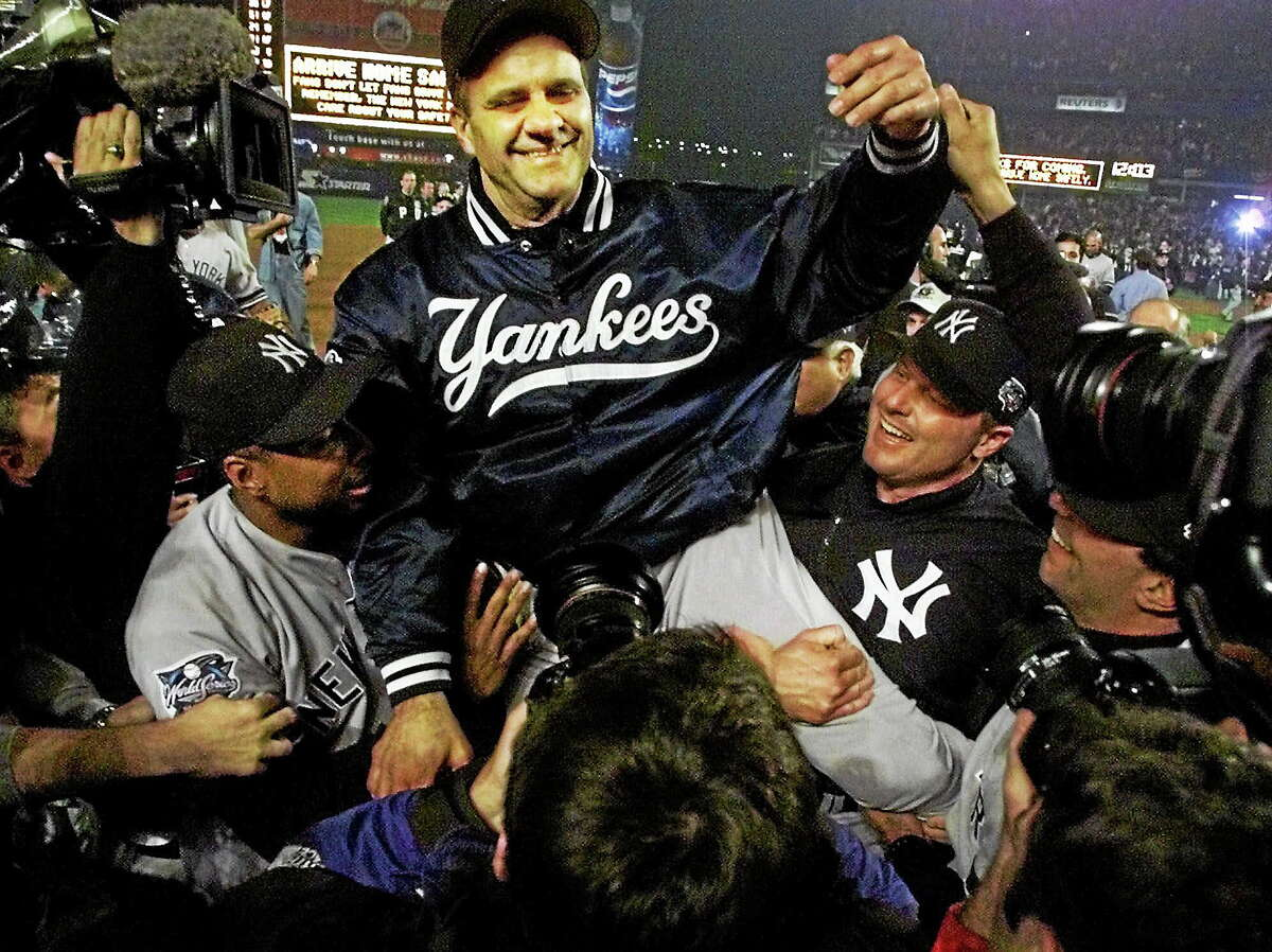 New York Yankees manager Joe Torre, center, is carried off the field by Bernie Williams, left, and Roger Clemens after winning the World Series by beating the New York Mets 4-2 in Game 5 at Shea Stadium in Queens on Oct. 27, 2000.