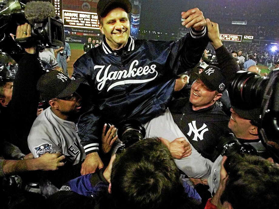 New York Yankees manager Joe Torre, center, is carried off the field by Bernie Williams, left, and Roger Clemens after winning the World Series by beating the New York Mets 4-2 in Game 5 at Shea Stadium in Queens on Oct. 27, 2000. Photo: Amy Sancetta — The Associated Press File Photo  / AP2000