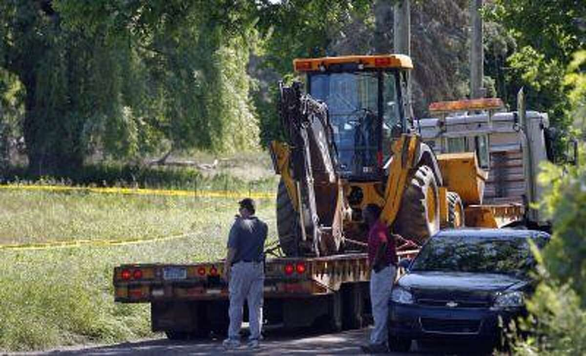 Federal investigators stand next to heavy equipment by a field which they are prepared to dig up for the remains of former Teamsters boss Jimmy Hoffa in Oakland Township, Michigan June 17, 2013. (Rebecca Cook/Reuters)