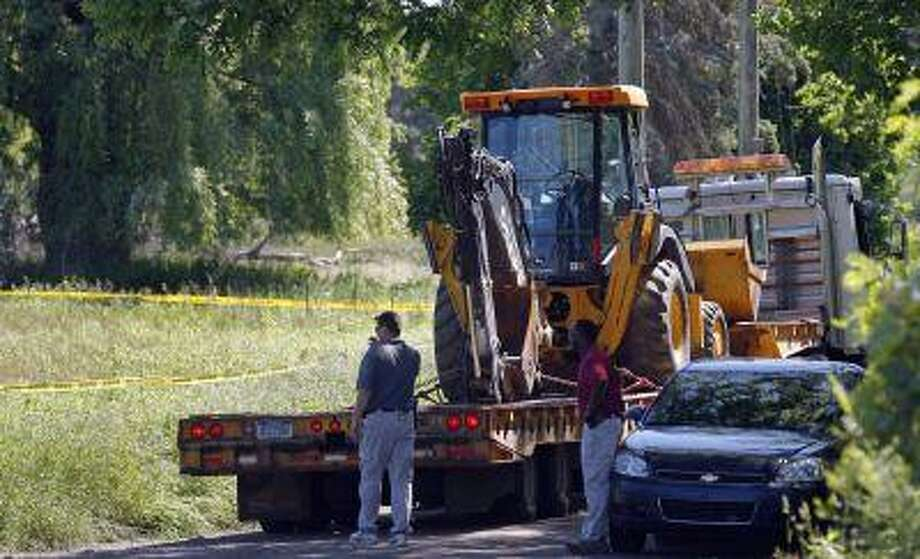 Federal investigators stand next to heavy equipment by a field which they are prepared to dig up for the remains of former Teamsters boss Jimmy Hoffa in Oakland Township, Michigan June 17, 2013. (Rebecca Cook/Reuters) Photo: REUTERS / X00064