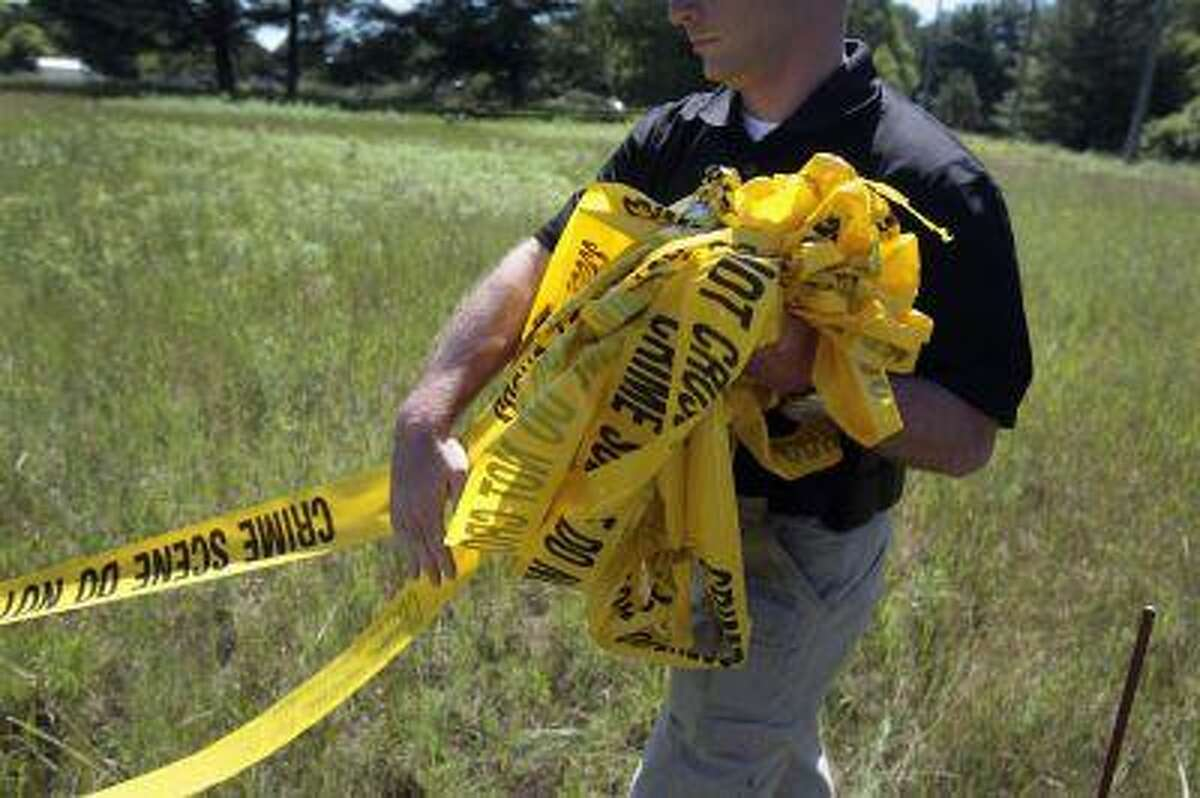 A federal investigator carries yellow crime tape at a field which investigators are prepared to dig up for the remains of former Teamsters boss Jimmy Hoffa in Oakland Township, Michigan June 17, 2013. (Rebecca Cook/Reuters)