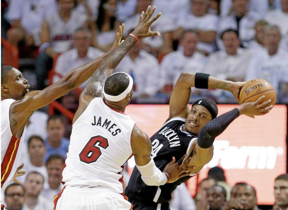 Brooklyn Nets forward Paul Pierce (34) looks for an open teammate as LeBron James and Chris Bosh, left, defend. Photo: Wilfredo Lee — The Associated Press  / AP