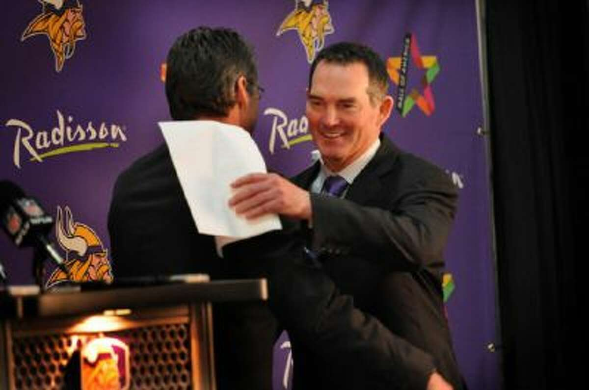 Vikings' new head coach Mike Zimmer, right, and general manager Rick Spielman, left, hug after Spielman introduces Zimmer at a news conference in the Winter Park Fieldhouse in Eden Prairie, Minn., Friday.