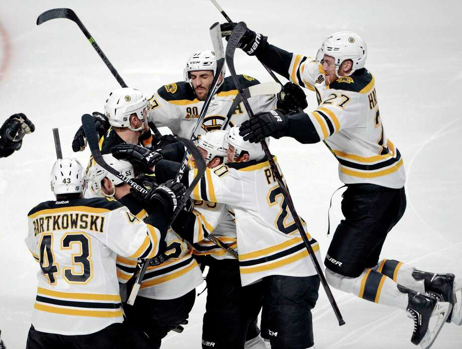 The Bruins' Matt Fraser is mobbed by teammates after scoring the game-winning goal against the Montreal Canadiens during the first overtime period in Game 4 in the second round of the NHL Stanley Cup playoffs Thursday. Photo: Ryan Remiorz — The Associated Press  / CP