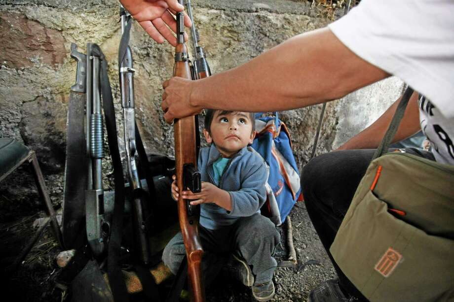 A child looks up as he tries to help his father arrange weapons at a checkpoint of the Self-Defense Council of Michoacan, (CAM), in Tancitaro, Mexico, Thursday, Jan. 16, 2014. Vigilantes in Michoacan state insist they won't lay down their guns until top leaders of a powerful drug cartel are arrested, defying government orders as federal forces try to regain control in a lawless region plagued by armed groups. (AP Photo/Felix Marquez) Photo: AP / AP