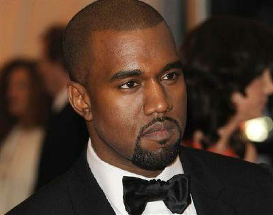 """In this Monday, May 7, 2012 photo, Kanye West arrives at the Metropolitan Museum of Art Costume Institute gala benefit, celebrating Elsa Schiaparelli and Miuccia Prada, in New York. West closed the three-day Governors Ball on New York's Randall's Island with a set that featured his familiar hits as well as a batch of new, darker tracks from his upcoming album. West kicked off his set Sunday night, June 9, 2013, with the song """"Black Skinhead,"""" with flashing visuals in the background, including the words """"not for sale."""" He later performed """"New Slaves."""" Both tracks will appear on """"Yeezus,"""" his sixth album out June 18. (AP Photo/Evan Agostini) Photo: AP / AGOEV"""