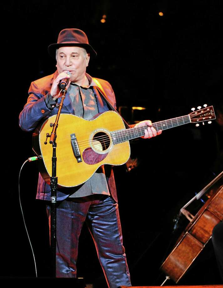 FILE - In this Thursday, April 17, 2014, file photo, musician Paul Simon performs at the 25th Anniversary Rainforest Fund benefit concert at Carnegie Hall in New York. Simon performed more than a dozen songs Wednesday night, May 7, 2014, at the Beacon Theatre in New York, where he was honored at the 2014 NYU Steinhardt Vision Award Gala. It was Simon's first public appearance since he and wife Edie Brickell were arrested on disorderly conduct charges. (Photo by Evan Agostini/Invision/AP, File) Photo: Evan Agostini/Invision/AP / Invision