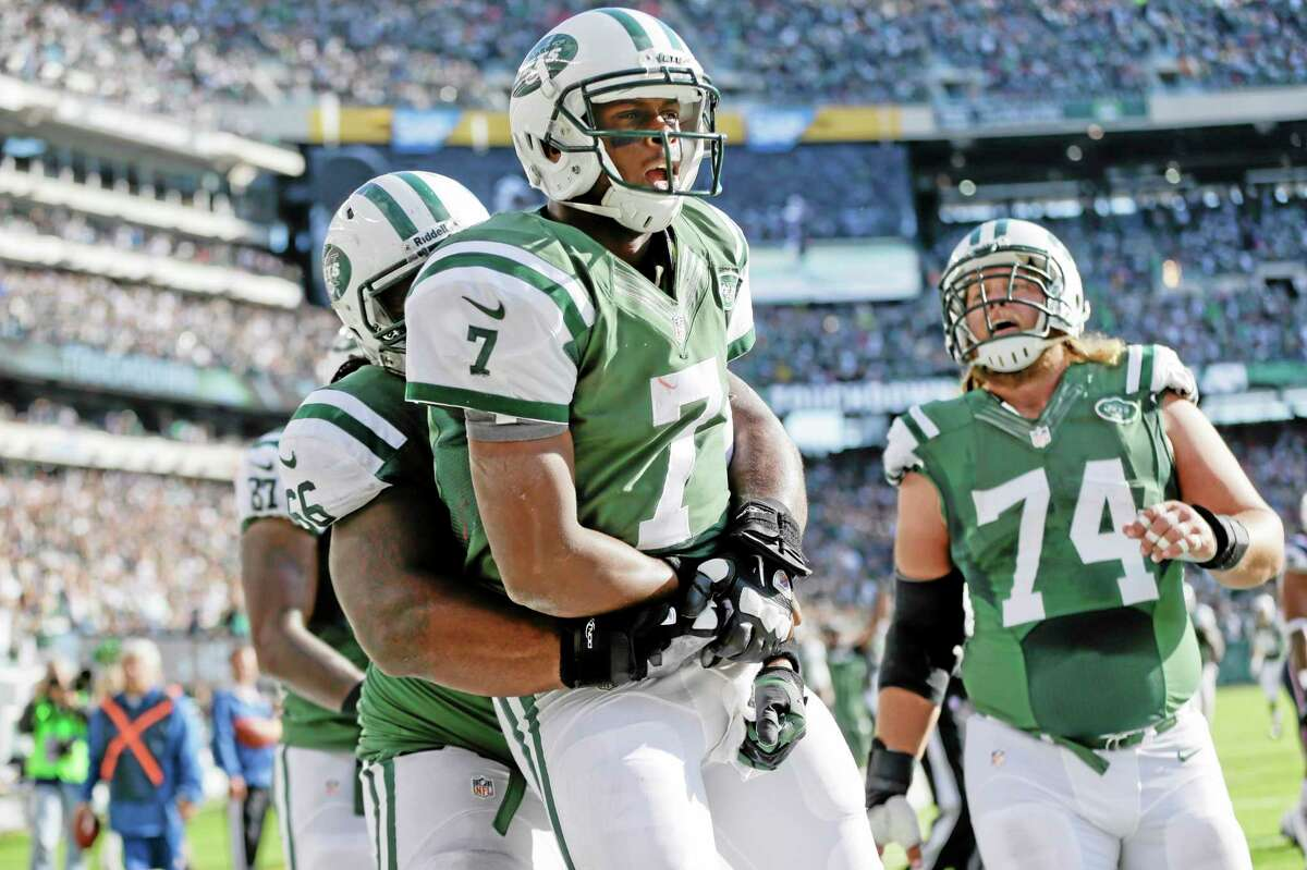 New York Jets quarterback Geno Smith (7) celebrates with Willie Colon and Nick Mangold (74) after rushing for a touchdown during the second half of Sunday's game in East Rutherford, N.J.
