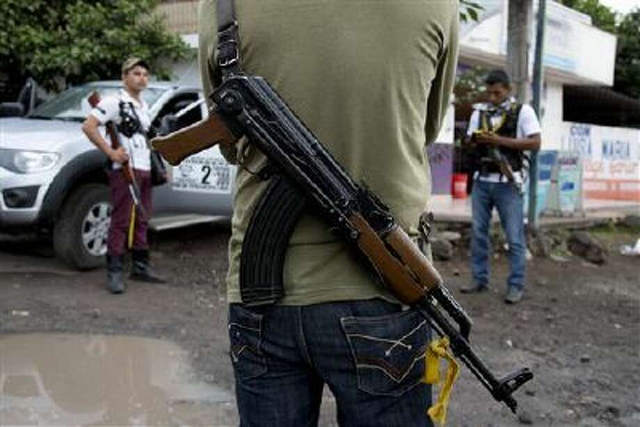 Armed men belonging to the Self-Defense Council of Michoacan stand guard at a checkpoint set up by the self-defense group at the entrance to the town of Antunez, Mexico. Photo: AP / AP
